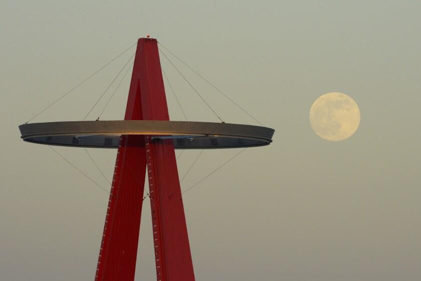The moon rises next the Los Angeles Angels' Big A sign.