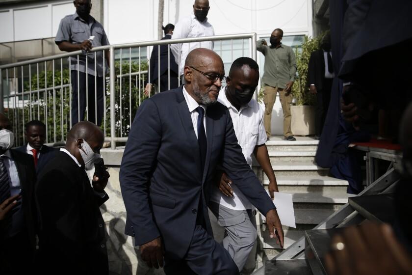 El nuevo primer ministro de Haití, Ariel Henry, sube escaleras acompañado de escoltas después de ser designado al cargo, el martes 20 de julio de 2021, en Puerto Príncipe. (AP Foto/Joseph Odelyn)