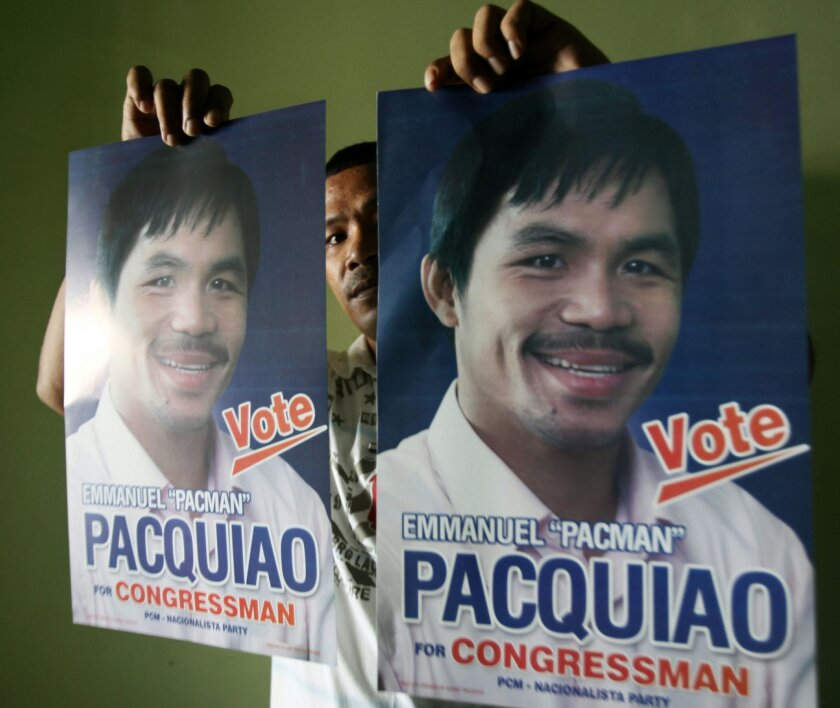 FILE - In this March 25, 2010 file photo, a staff member of the People's Champ Movement shows campaign posters of Filipino boxing great Manny Pacquiao at his office in General Santos city southern Philippines. Pacquiao has been an inspiration for millions of Filipinos not just as a boxer, but as a