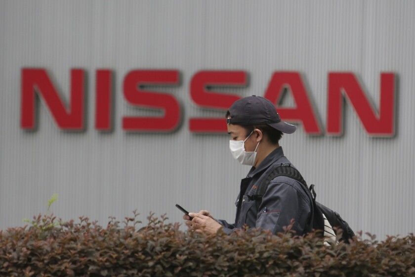 A man walks past the corporate logos at the global headquarters of Nissan Motor Co., Ltd. in Yokohama near Tokyo, Thursday, May 21, 2020. Nissan says it is developing a new way to produce auto parts, highlighting the Japanese automaker's engineering finesse, even as it struggles to recover from a scandal centered around its former chairman, Carlos Ghosn. (AP Photo/Koji Sasahara)