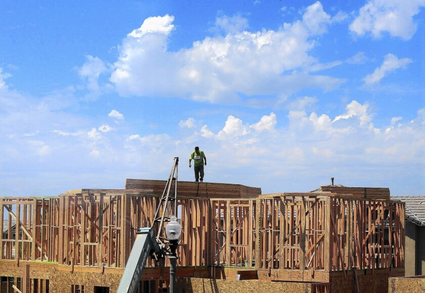 A framer works on the roof line of a new home under construction Tuesday at the William Lyon Homes site in the Pavilion Park development in Irvine.