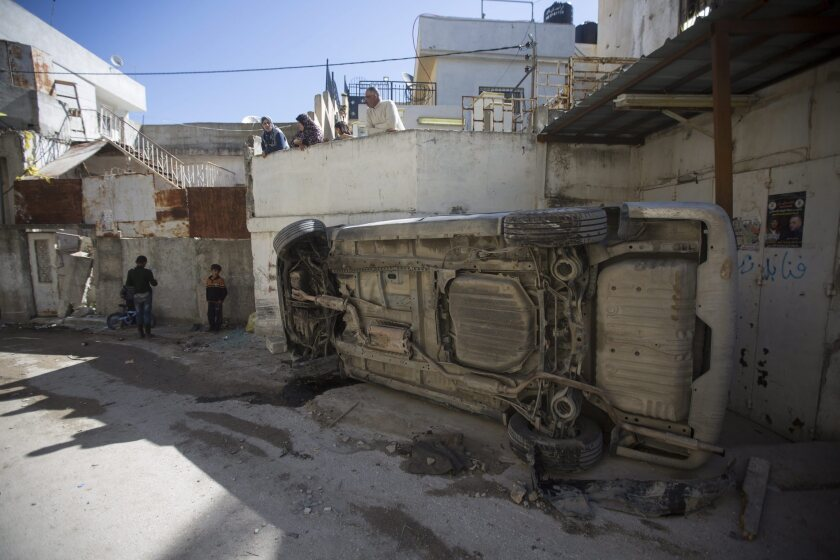 A car lies on its side in the Qalandia refugee camp in the West Bank on Tuesday, the day of the funeral for Iyad Sajadiyya, who was killed by Israeli forces in the camp to look for a missing soldier.