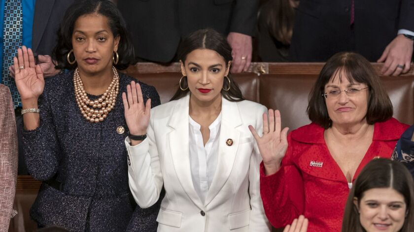 Rep. Alexandria Ocasio-Cortez (D-N.Y.), center, is flanked by Reps. Jahana Hayes (D-Conn.), left, and Ann McLane Kuster (D-N.H.) as they are sworn in on the opening day of the 116th Congress.