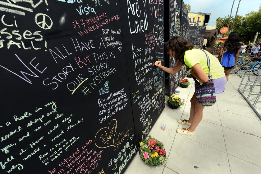 UC Santa Barbara student Samantha Lepore writes on the Wall of Remembrance near the site where seven people were killed and 13 wounded in a shooting rampage in the college town of Isla Vista, Calif.