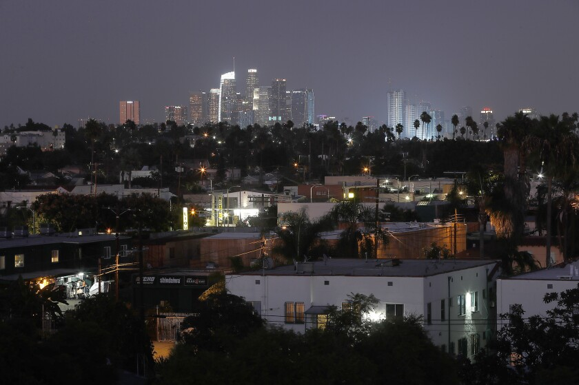 Dusk descends on the residential streets of the Crenshaw District in South L.A. with the downtown Los Angeles skyline in the background.