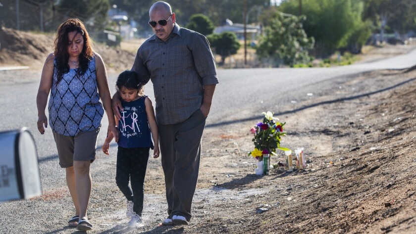 Carlos Garibay, his daughter Melanie and wife Penny Garibay walk close together after dropping off a bouquet of flowers at the scene where two boys were killed Tuesday in an alleged street racing incident. Melanie Garibay was a classmate of one of the boys.