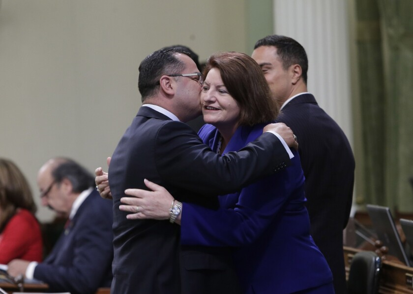 Assemblywoman Toni Atkins (D-San Diego) is hugged by Assemblyman V. Manuel Pérez (D-Coachella) before being sworn in as Assembly speaker at the Capitol on Monday.