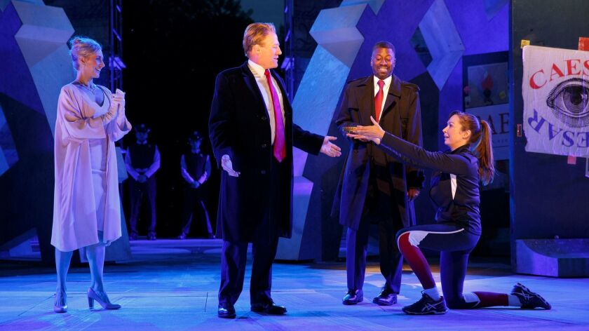 """Gregg Henry, second from left, portrays a Trump-esque Julius Caesar in the Public Theatre production of """"Julius Caesar."""" Also pictured, from left: Tina Benko and Melania Trump-like Calpurnia, Teagle F. Bougere as Casca, and Elizabeth Marvel as Marc Anthony."""