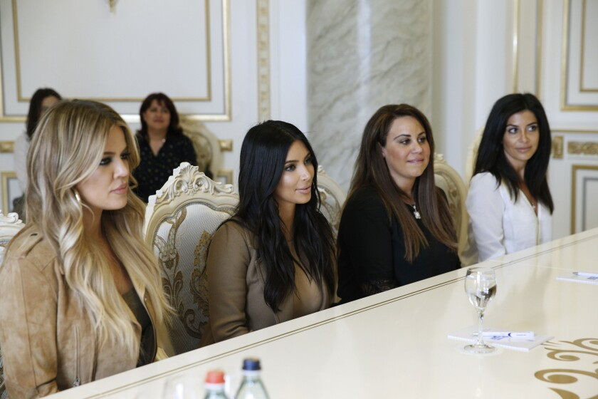 Reality TV stars Khloe Kardashian, left, and Kim Kardashian, second left, are seen listening to Armenia's prime minister during a meeting Thursday in Yerevan in this photo released by the Armenian Government Press Service.
