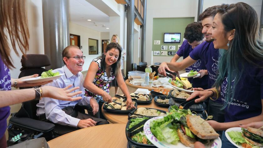 Glen and Rocio Middleton, center, serve lunch to youth participating in the three-week Hands of Peace summer program in Carlsbad. The program brings together Americans, Israelis and Palestinians for dialogue, conflict resolution and leadership training.
