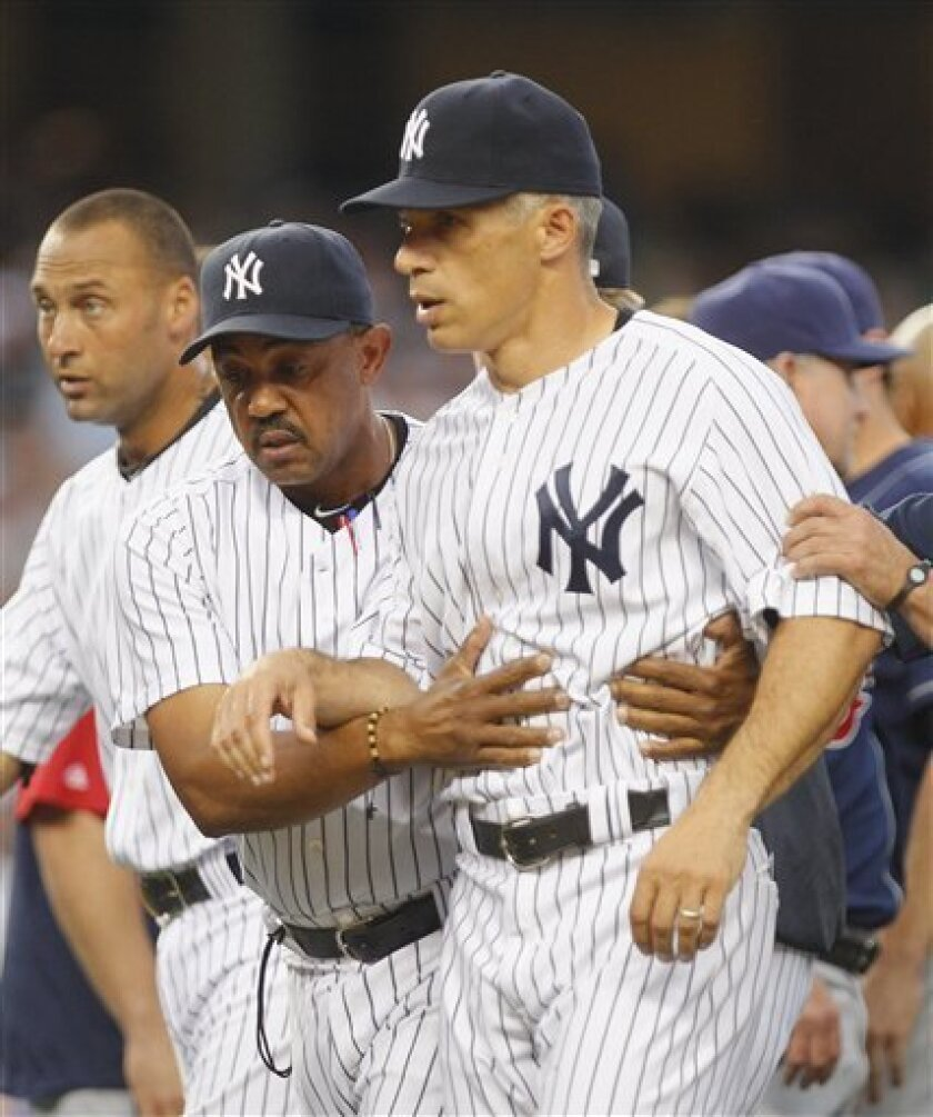 New York Yankees Manager Joe Girardi, right, is led away from Cleveland Indians pitcher Fausto Carmona by Yankees coach Tony Pena, front left, after Carmona hit Yankees' Mark Teixeira with a pitch in the second inning of their Major League Baseball game at Yankee Stadium in New York, Friday, June 10, 2011. Both benches emptied during the confrontation. (AP Photo/Paul J. Bereswill)