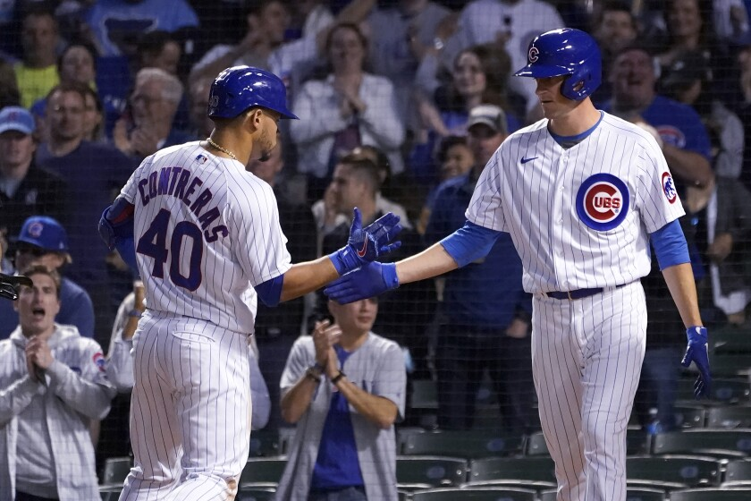 Chicago Cubs' Willson Contreras (40) and Kyle Hendricks celebrate at home after they scored on Contreras' home run off San Diego Padres starting pitcher Ryan Weathers during the fifth inning of a baseball game Tuesday, June 1, 2021, in Chicago. (AP Photo/Charles Rex Arbogast)