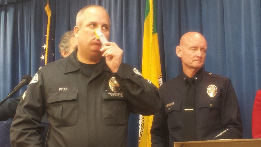 Los Angeles Police Department Officer Don Inman rubs a swab around the inside of his mouth to demonstrate an on-the-spot drug test being used by law enforcement to deter people from driving under the influence of drugs.