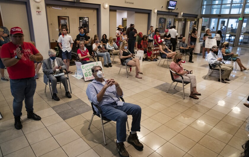 Riverside County residents watch video monitors of an emergency Riverside County Board of Supervisors meeting last month.