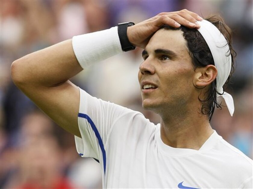 Spain's Rafael Nadal reacts after defeating Ryan Sweeting of the US at the All England Lawn Tennis Championships at Wimbledon, Wednesday, June 22, 2011. (AP Photo/Kirsty Wigglesworth)