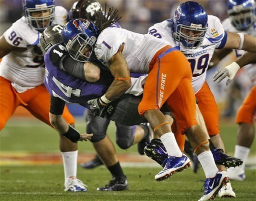 TCU quarterback Andy Dalton (14) is sacked by Boise State cornerback Kyle Wilson (1) during the first quarter of the Fiesta Bowl NCAA college football game Monday, Jan. 4, 2010, in Glendale, Ariz. (AP Photo/Matt York)