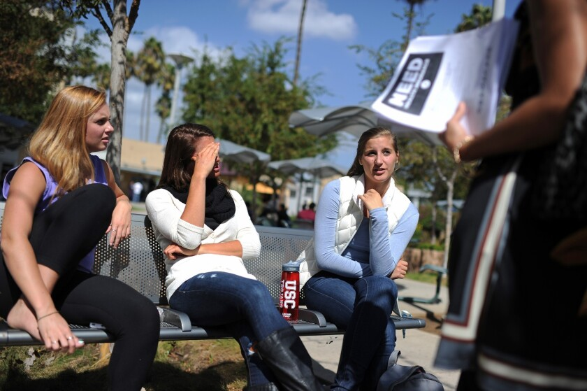 Students Amanda McComas, left, Rose Marie Chute and Sari Schwartz discuss Obamacare with Lisa Fiori, a supporter of the Affordable Care Act, at an education and awareness event on the law on the campus of Santa Monica City College.