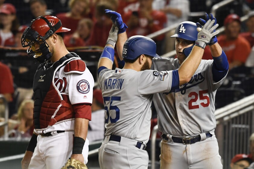 Los Angeles Dodgers' Russell Martin (55) celebrates with David Freese (25) after hitting a two-run home run off Washington Nationals relief pitcher Hunter Strickland during the ninth inning in Game 3 of a baseball National League Division Series on Sunday, Oct. 6, 2019, in Washington. At left is Nationals catcher Kurt Suzuki. (AP Photo/Susan Walsh)
