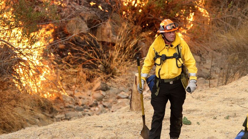 A Los Angeles fireman on La Tuna Canyon Road on Friday. The La Tuna fire placed about 400 Glendale residents under a mandatory evacuation order.