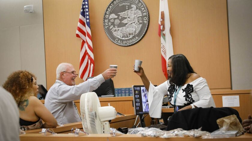 Superior Court judicial secretary Steve Silva, left, toasts the retirement of courtroom clerk Frieda McCurley at her farewell party on Friday.