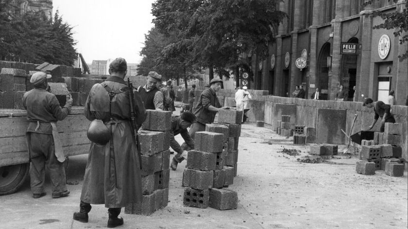 East German soldiers look over workers building the first segments of the Berlin Wall on Aug. 13, 1961.
