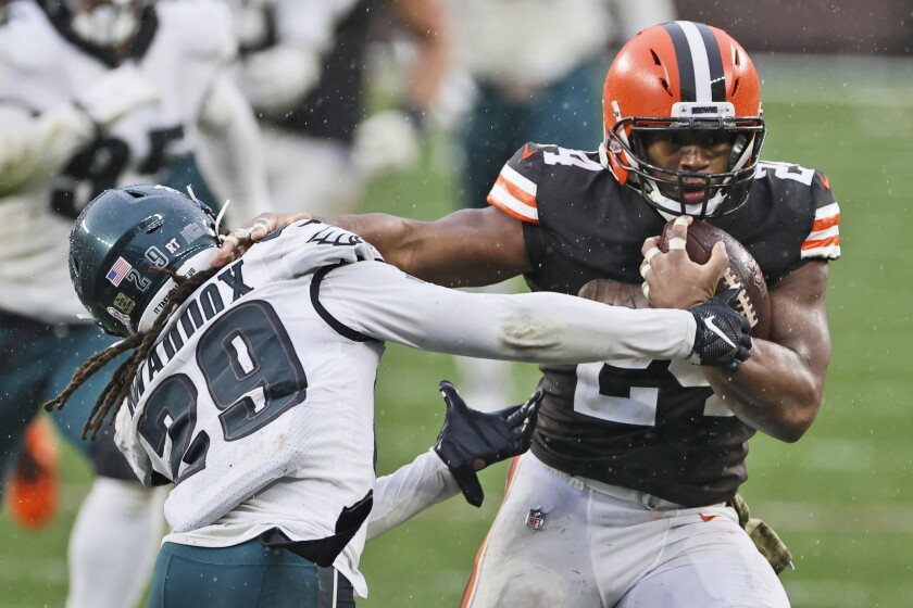 Cleveland Browns running back Nick Chubb (24) breaks a tackle by Philadelphia Eagles cornerback Avonte Maddox (29) during the second half of an NFL football game, Sunday, Nov. 22, 2020, in Cleveland. (AP Photo/Ron Schwane)