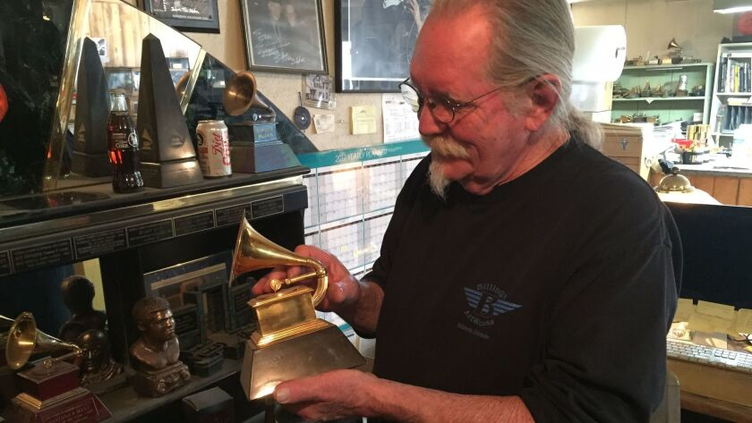 John Billings holds one of the Grammys he's made. Each one takes 15 hours of work from Billings and his three-man team.