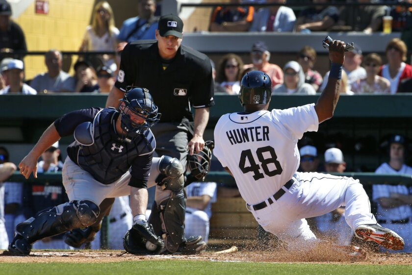 Detroit Tigers' Torii Hunter (48) begins his slide as New York Yankees catcher Brian McCann, left, waits to make the tag at home in front of umpire Andy Fletcher during the third inning of an exhibition spring training baseball game in Lakeland, Fla., Friday, Feb. 28, 2014. Hunter was attempting to