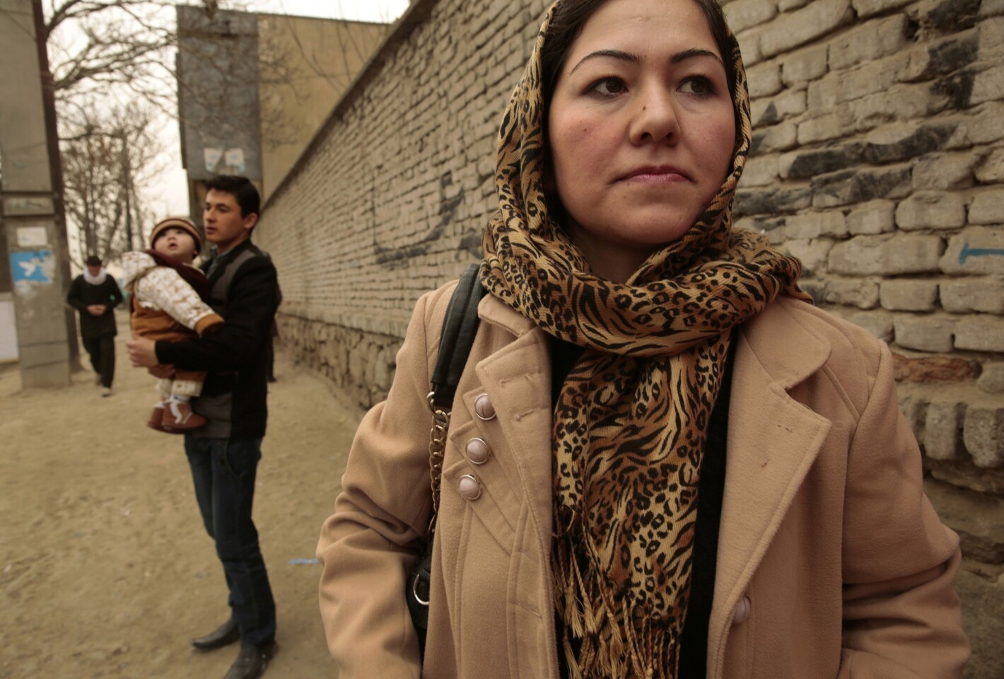 """Ghazalan Koofi, 26, waits for a ride to work as her brother-in-law Shafiq Azizi holds her baby, Ahmad, 11 months. Despite growing up under Taliban rule, Koofi was able to graduate from high school, and is now studying literature in college. But with U.S. combat troops leaving Afghanistan next year, Koofi and other Afghan women worry that their freedoms will begin to erode. """"We are entering a very dangerous period for women,"""" Koofi says."""