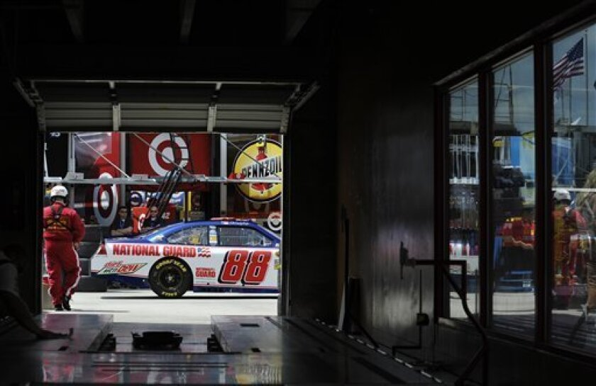 Dale Earnhardt Jr. (88) drives his car through the garage area during practice for Sunday's NASCAR Sprint Cup Series auto race at Atlanta Motor Speedway, Friday, Aug. 31, 2012, in Hampton, Ga. (AP Photo/Rainier Ehrhardt)