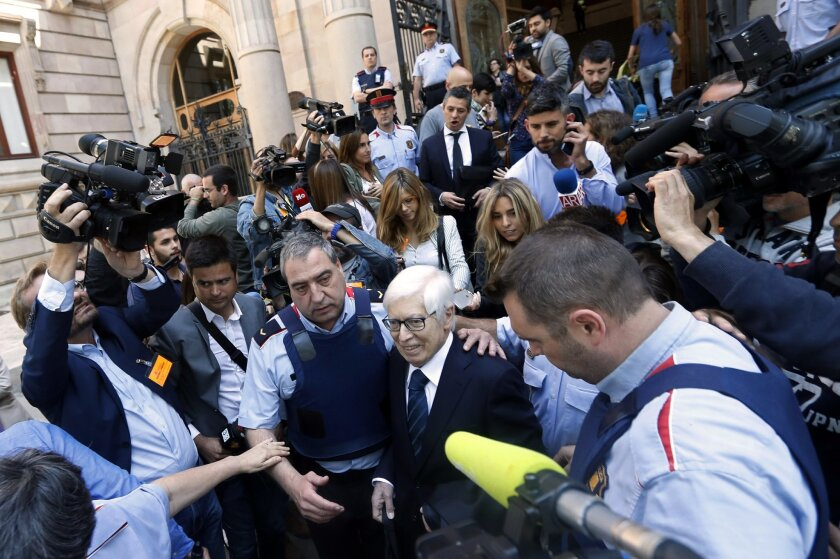 Lionel Messi's lawyer Enrique Bacigalupo, center right, is surrounded by journalists on leaving a court in Barcelona, Spain, Tuesday May 31, 2016. Lionel Messi's tax trial began Tuesday with the player deciding not to appear in court for early proceedings. Messi is facing a prison sentence of nearl