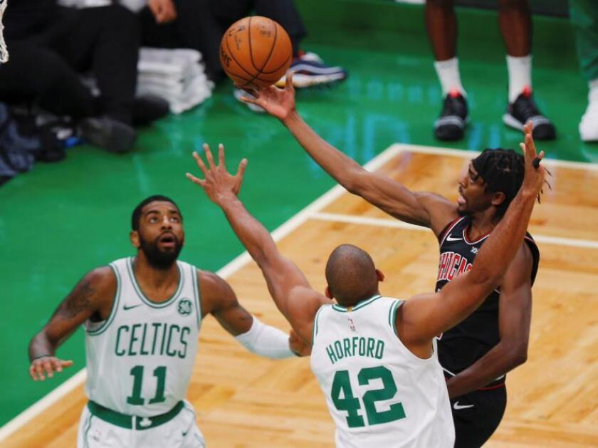 El alero Justin Holiday (d) de Chicago lanza el balón ante la defensa de Kyrie Irving (i) y Al Horford (c) de Boston Celtic, durante un partido. EFE/Archivo