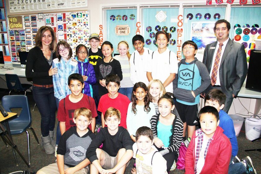 Sage Canyon teacher Paris Esmaili, left, and Joshua Barker, branch manager of Wells Fargo, right, with the pilot class for a new business program in the Del Mar Union School District.