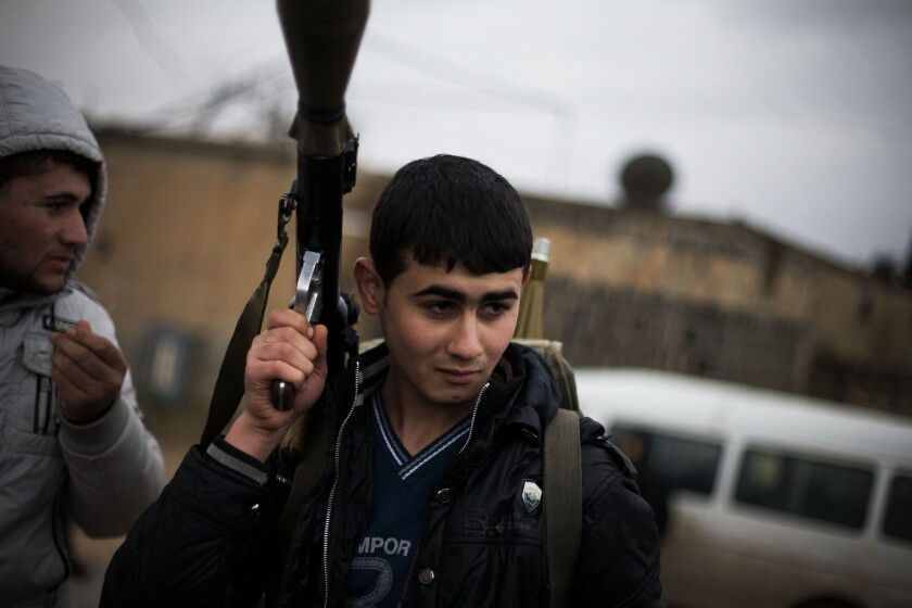 A file photo shows a Free Syrian Army fighter with his weapon as he prepares for an advance near Azaz, Syria. An Al-Qaeda-linked group has now taken control of the town.