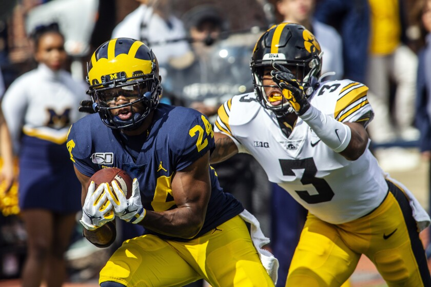 Michigan defensive back Lavert Hill (24) intercepts a pass intended for Iowa wide receiver Tyrone Tracy, Jr. (3) in the second quarter of an NCAA college football game in Ann Arbor, Mich., Saturday, Oct. 5, 2019. (AP Photo/Tony Ding)