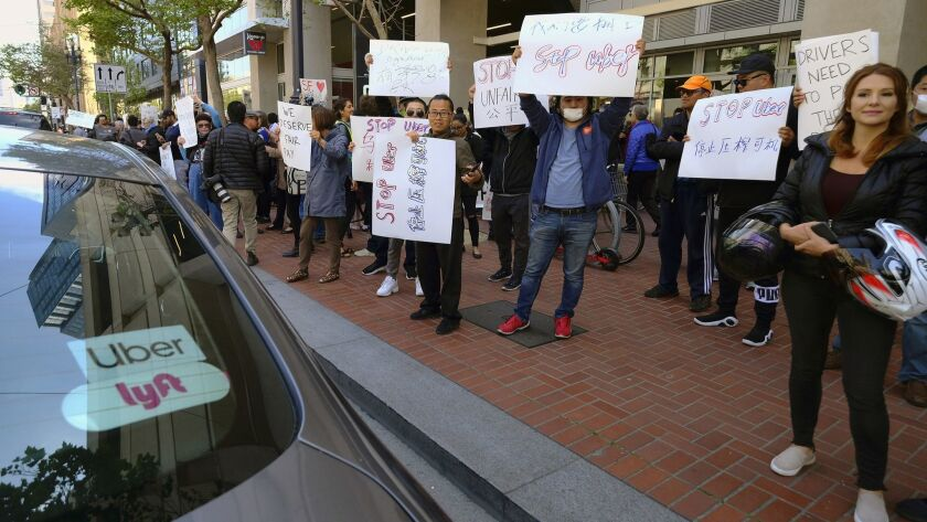 FILE - In this May 8, 2019,, file photo, Uber and Lyft drivers carry signs during a demonstration ou