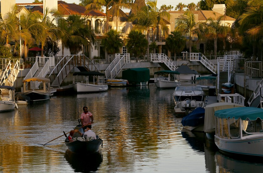 A gondolier rows visitors through the canals of Naples, a bayside community in Long Beach.