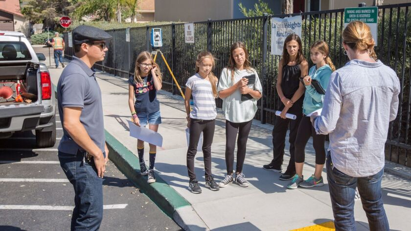 SWPPP interns (5th/6thth graders from La Costa Heights) on Oct. 3 prepare to begin the topographic survey for the bioswale project in front of the school. Chris Radder of Webb Cleff Architecture, left, and Ryan Post of ATC Design Group provide an overview of the survey work.