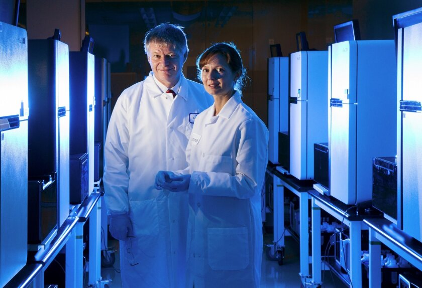 Dr. Stephen Kingsmore, left, president and CEO of the newly formed Rady Pediatric Genomics and Systems Medicine Institute, and Tina Hambuch, Ph.D., right, director of clinical services at Illumina, are near a group of genomic sequencing machines at Illumina. The time it takes to sequence a genome has been reduced to 26 hours.