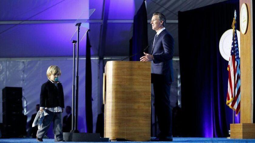 Gov. Gavin Newsom delivers his inaugural address as his son Dutch, 2, walks onstage Monday.