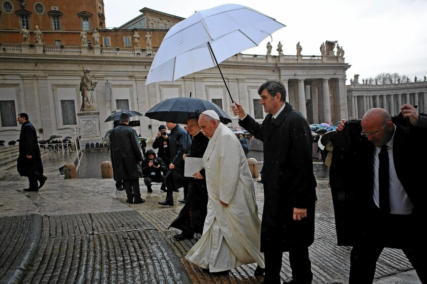 Pope Francis arrives amid a rain shower Wednesday in St. Peter's Square to lead his traditional weekly general audience.