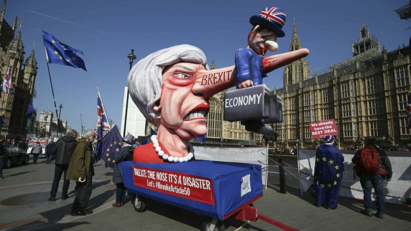 Anti-Brexit demonstrators with an effigy of British Prime Minister Theresa May near College Green at