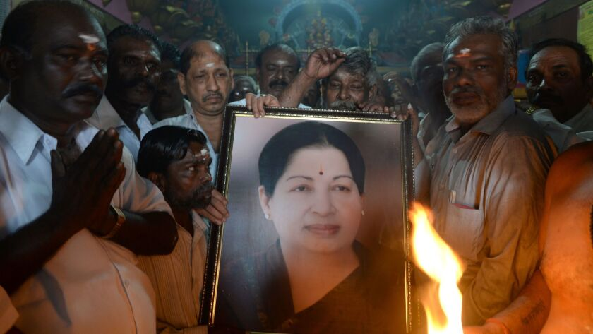 Supporters hold a photograph of Jayaram Jayalalithaa as they offer prayers for her well-being at a temple in Mumbai, India.
