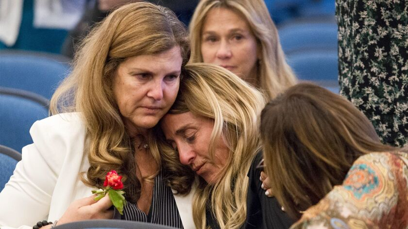 Elizabeth Gilbert, center, the wife of Dr. Ronald Gilbert, who was shot and killed in 2013, is comfo