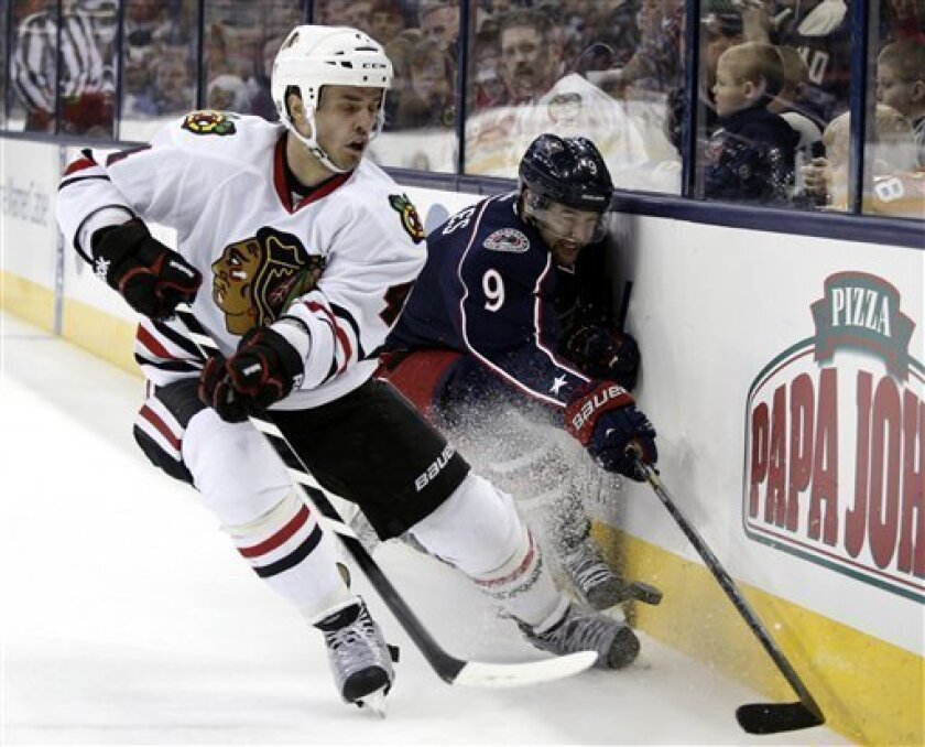 Chicago Blackhawks' Niklas Hjalmarsson, left, of Sweden works for the puck against Columbus Blue Jackets' Colton Gillies during the second period of an NHL hockey game in Columbus, Ohio, Thursday, March 14, 2013. (AP Photo/Paul Vernon)