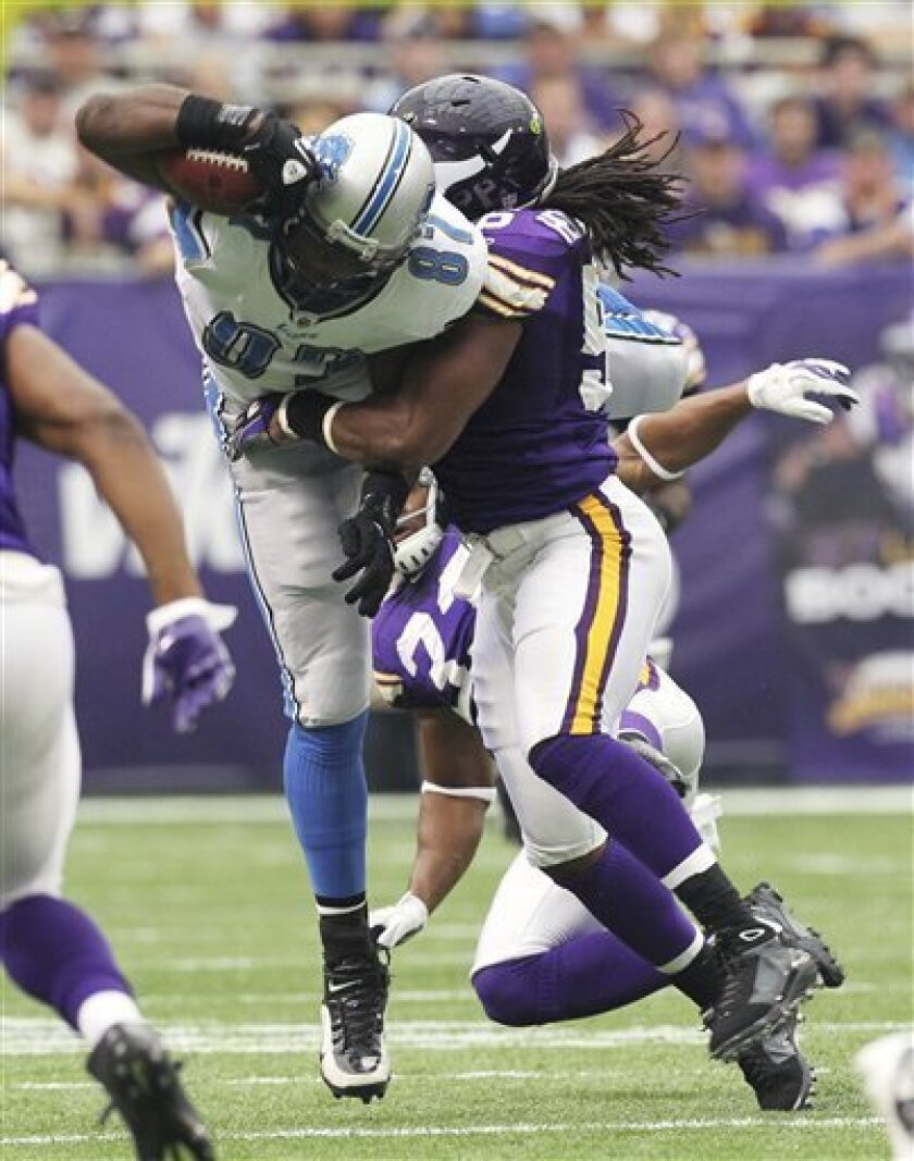 Detroit Lions tight end Brandon Pettigrew (87) is tackled by Minnesota Vikings linebacker E.J. Henderson after making a reception during the first half an NFL football game Sunday, Sept. 25, 2011, in Minneapolis. (AP Photo/Genevieve Ross)