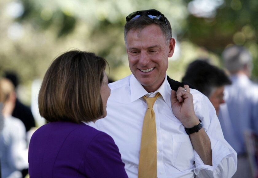 Rep. Scott Peters, pictured smiling as he talks with Rep. Susan Davis at a Balboa Park rally.