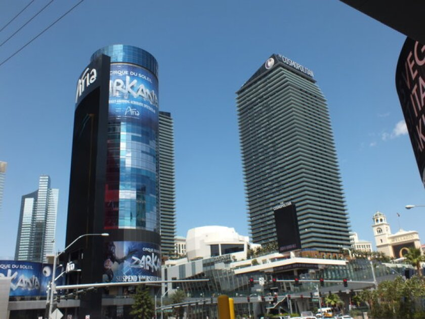 The Harmon, left, a blue-glass hotel tower that never opened, rises just south of the Cosmopolitan along Las Vegas Boulevard. The building has become a giant billboard for CityCenter attractions.