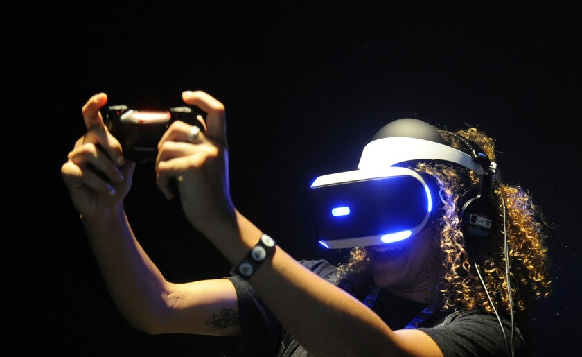 Sianna Hasenberg plays with Sony's PlayStation VR at the Electronic Entertainment Expo in 2015. The headset is due for release in 2016.