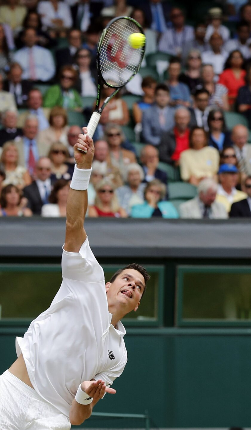 Milos Raonic of Canada returns to Roger Federer of Switzerland during their men's semifinal singles match on day twelve of the Wimbledon Tennis Championships in London, Friday, July 8, 2016. (AP Photo/Ben Curtis)